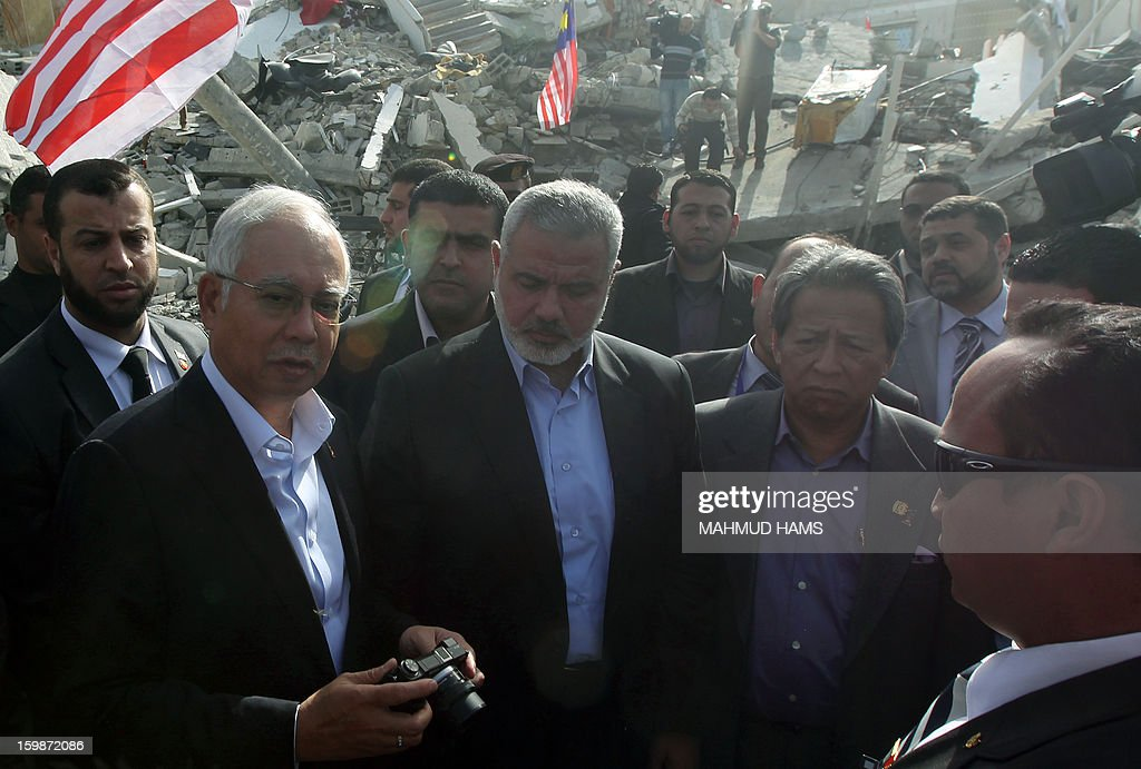 Malaysian Prime Minister Najib Razak (L) and Gaza's Hamas prime minister Ismail Haniya (C) are seen visiting the government building desteoyed during the Israeli and Hamas conflict November 14-21, 2012, in Gaza city on January 22, 2013. Razak pledged solidarity with the Palestinians on his first trip to Gaza, and backed reconciliation efforts between Hamas and Fatah.