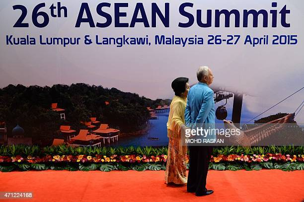 Malaysian Prime Minister Najib Razak and his wife Rosmah Mansor stand as they wait for a group photo before a gala dinner in honour of ASEAN heads of...