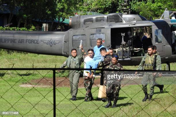 Malaysian seaman Abdurahim bin Sumas is carried by military personnel to a waiting helicopter at a military hospital in Jolo town Sulu province in...