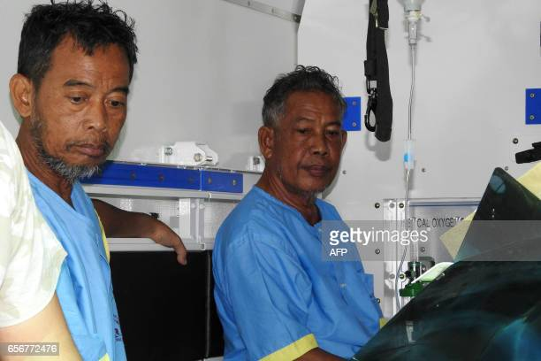 Malaysian seamen Tayudin Anjut and Abdurahim bin Sumas sit inside an ambulance before being airlifted from a military hospital in Jolo town Sulu...