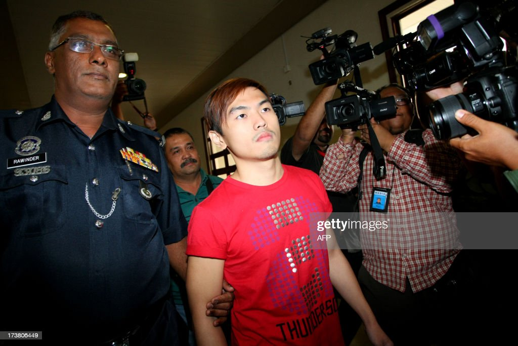 Malaysian sex blogger Alvin Tan (C) is escorted by Malaysian police as he arrives at the High Court in Kuala Lumpur on July 18, 2013. A Malaysian couple, known for a sexually explicit blog, were charged with sedition after they caused outrage by posting a Ramadan greeting on Facebook which showed them eating pork.