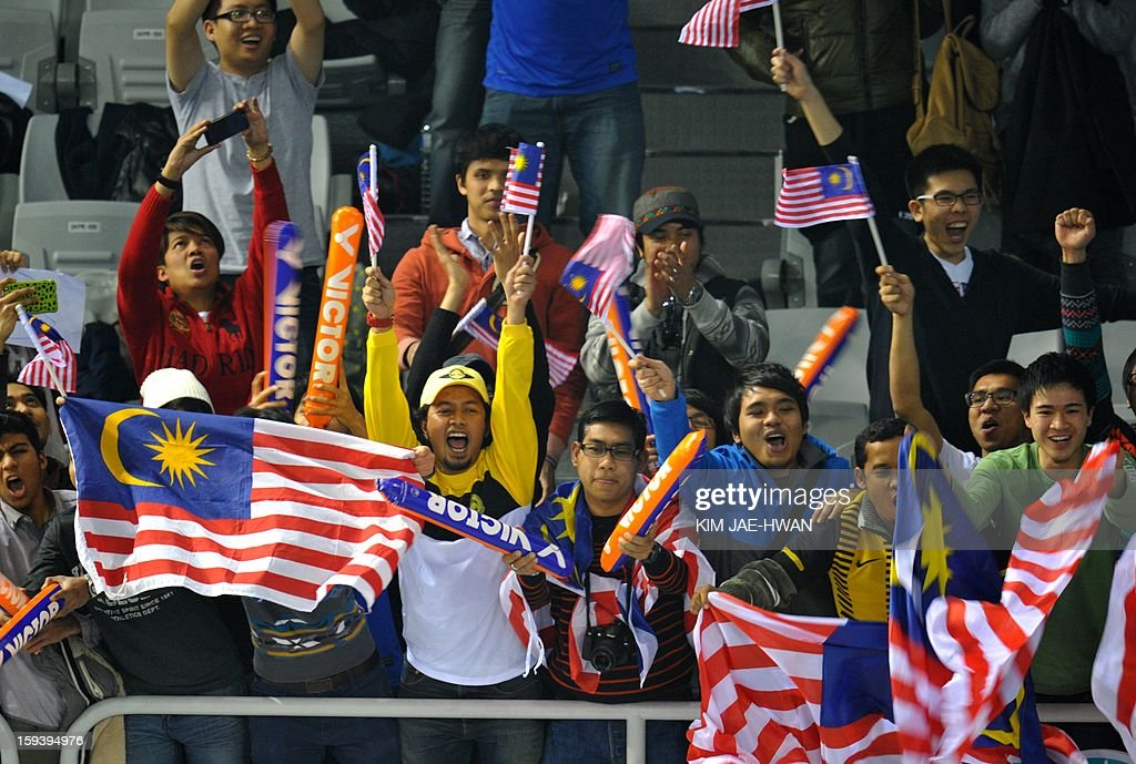 Malaysian supporters wave flags during Lee Chong Wei's men's singles badminton match against Pengyu Du of China during the finals of the Korea Open at Seoul on January 13, 2013.
