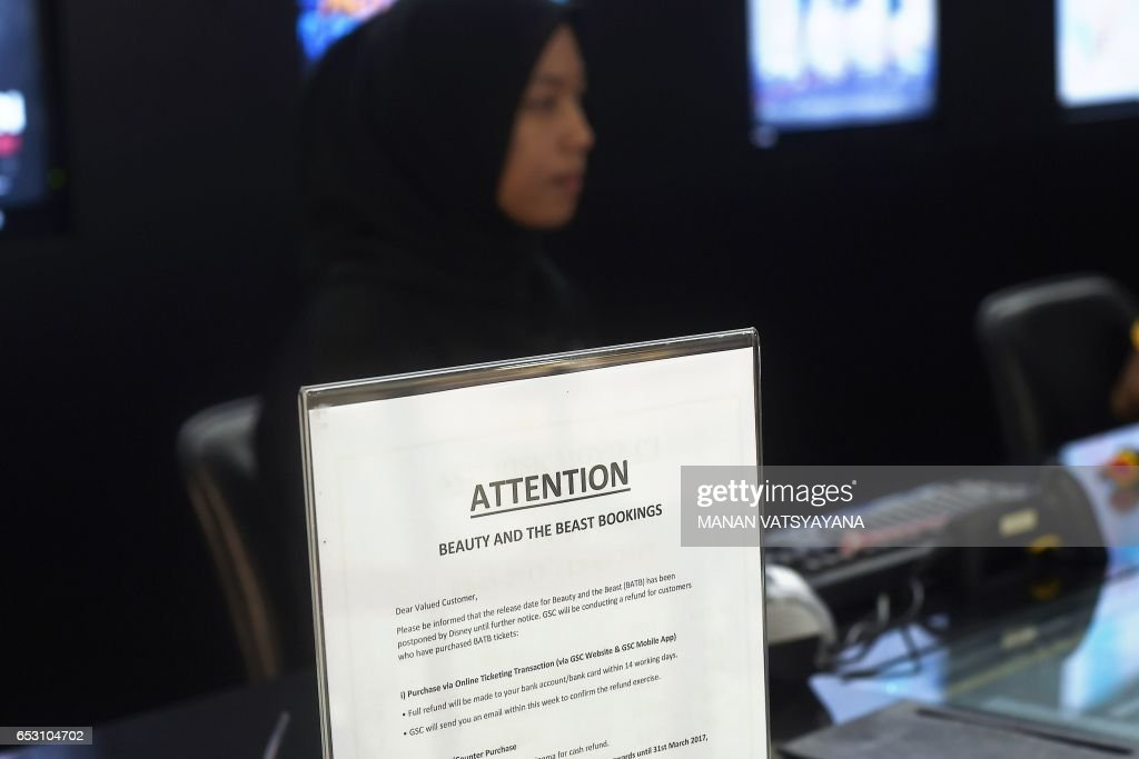 A Malaysian ticket-seller sits behind a notice displayed regarding the release of the film 'Beauty and the Beast' at a Golden Screen Cinemas theatre in Kuala Lumpur on March 14, 2017. Malaysian censors have reportedly cut out a 'gay moment' in the Disney film 'Beauty and the Beast' before agreeing to its release in the Muslim-majority nation. / AFP PHOTO / Manan VATSYAYANA
