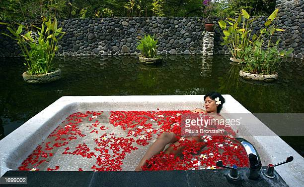 Malaysian tourist enjoys a jacuzzi filled with flower pedals after her herbal body scrub at the Mandara Spa at the Chedi Hotel July 31 2002 in Ubud...