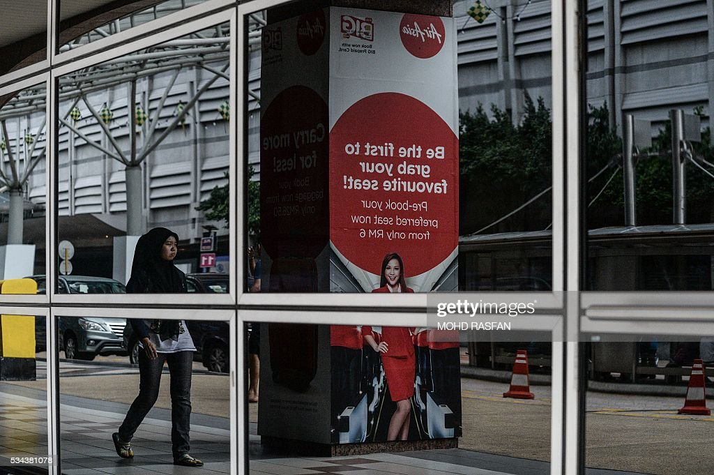 A Malaysian woman and an AirAsia advertisement are relected on the windows at Kuala Lumpur Sentral railway station in Kuala Lumpur on May 26, 2016. Malaysia's Budget carrier AirAsia was expected to announce its first quarter results on the back of lower oil prices on May 26. / AFP / MOHD