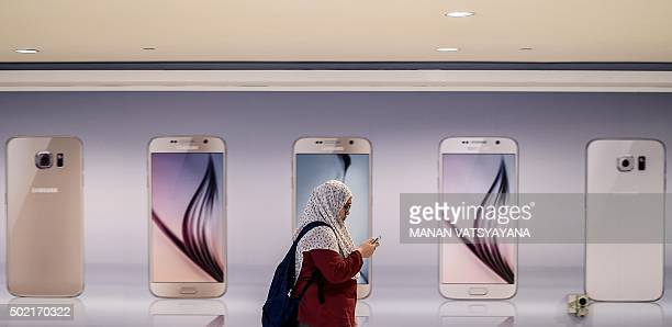 A Malaysian woman checks her mobile phone as she walks past an advertisement for smartphones in Kuala Lumpur on December 21 2015 AFP PHOTO / MANAN...