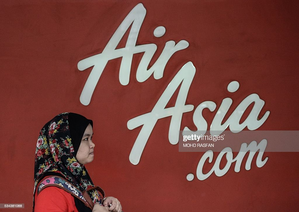 A Malaysian woman walks past an AirAsia advertisement at Kuala Lumpur Sentral railway station in Kuala Lumpur on May 26, 2016. Malaysia's Budget carrier AirAsia was expected to announce its first quarter results on the back of lower oil prices on May 26. / AFP / MOHD