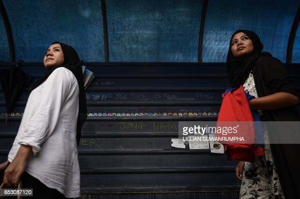 TOPSHOT Malaysian women walk past graffiti left by members of the media opposite the gate of the forensics wing of the Hospital Kuala Lumpur where...