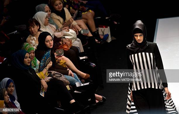 Malaysian women wearing 'hijabs' watch as a model presents creations by designer Jubahsouq at the Islamic Fashion Festival during 2014 Malaysia...
