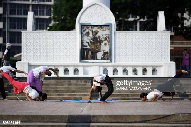 Malaysian yoga practitioners perform exercises during an event to mark International Yoga Day in Kuala Lumpur on June 21 2017 International Yoga Day...