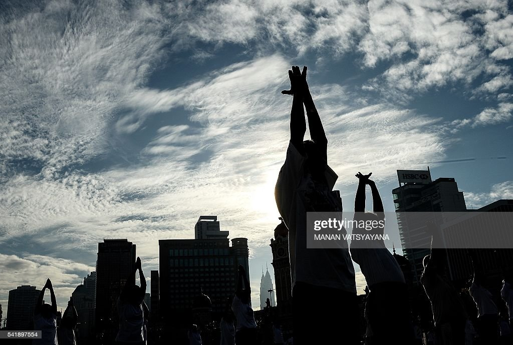 TOPSHOT Malaysian Yoga practitioners perform yoga exercises during an event to mark the International Yoga Day at the iconic Sultan Abdul Samad...