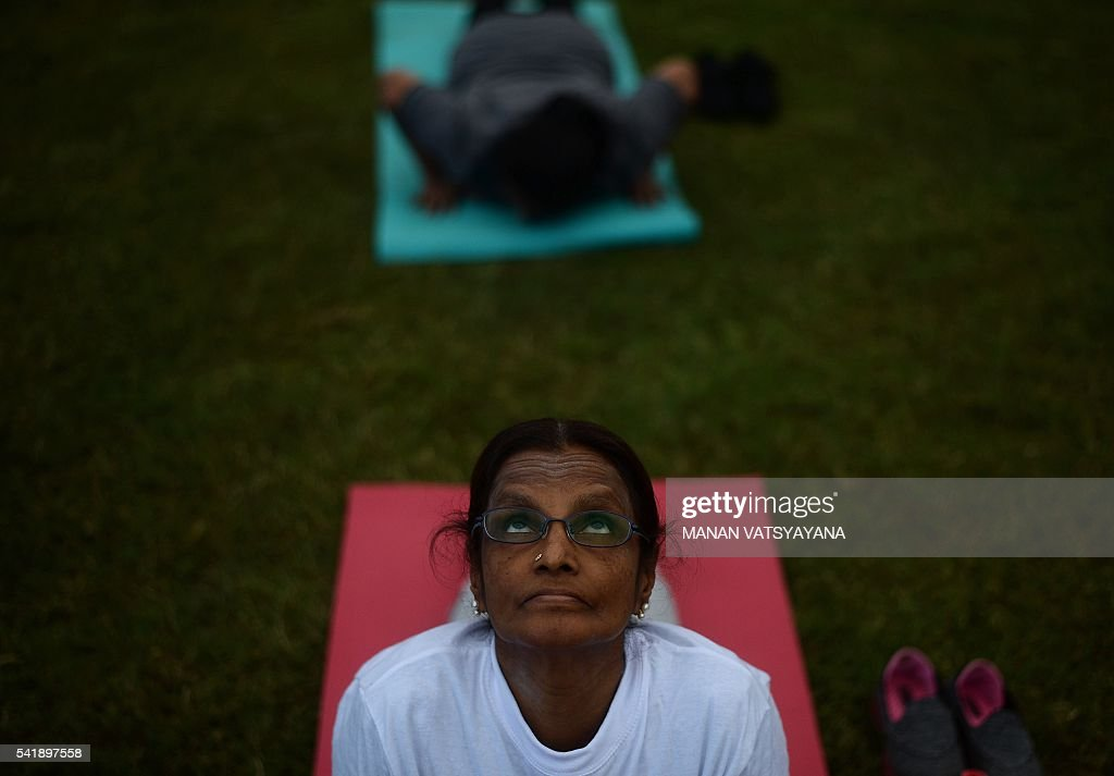 Malaysian Yoga practitioners perform yoga exercises during an event to mark the International Yoga Day at the iconic Sultan Abdul Samad building in...