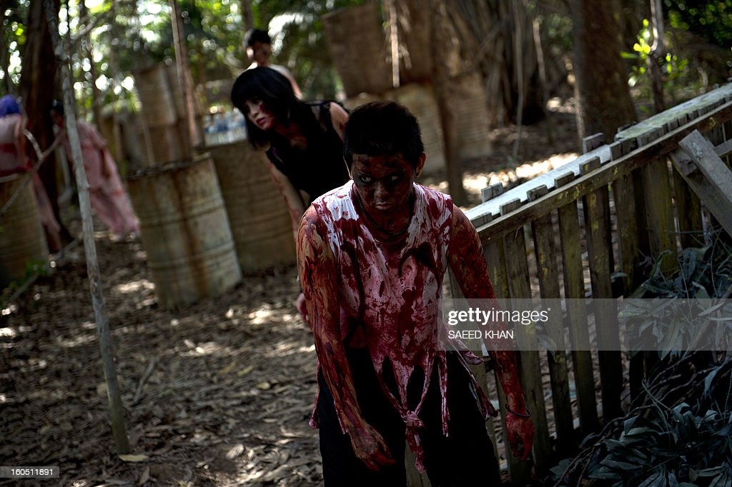 A Malaysian youngster dressed as zombie chases participants of a zombie run inside a jungle in the outskirts of Kuala Lumpur on February 2, 2013. The zombies' goal is to take away runners' tags before they reach the race's finishing point in the one-day event. Zombie runs are already popular in the US and other countries. Malaysia has long had an interest in the supernatural rooted in age-old legends. Horror films have become increasingly popular in recent years after effectively being banned in the Muslim-majority country for three decades for celebrating the other-worldly in violation of Islamic teachings.But since popular culture was allowed to relax in the past decade, horror movies have sprouted. In 2011, the genre made up more than a third of domestic movies. AFP PHOTO / Saeed KHAN