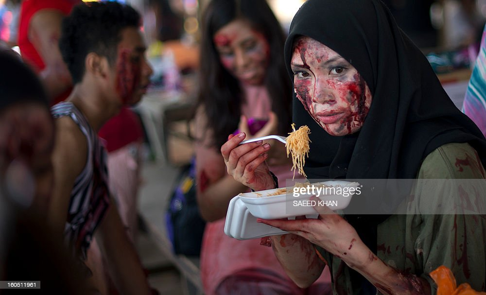 A Malaysian youngster dressed as zombie eats noodles during a zombie run inside a jungle in the outskirts of Kuala Lumpur on February 2, 2013. The zombies' goal is to take away runners' tags before they reach the race's finishing point in the one-day event. Zombie runs are already popular in the US and other countries. Malaysia has long had an interest in the supernatural rooted in age-old legends. Horror films have become increasingly popular in recent years after effectively being banned in the Muslim-majority country for three decades for celebrating the other-worldly in violation of Islamic teachings.But since popular culture was allowed to relax in the past decade, horror movies have sprouted. In 2011, the genre made up more than a third of domestic movies. AFP PHOTO / Saeed KHAN
