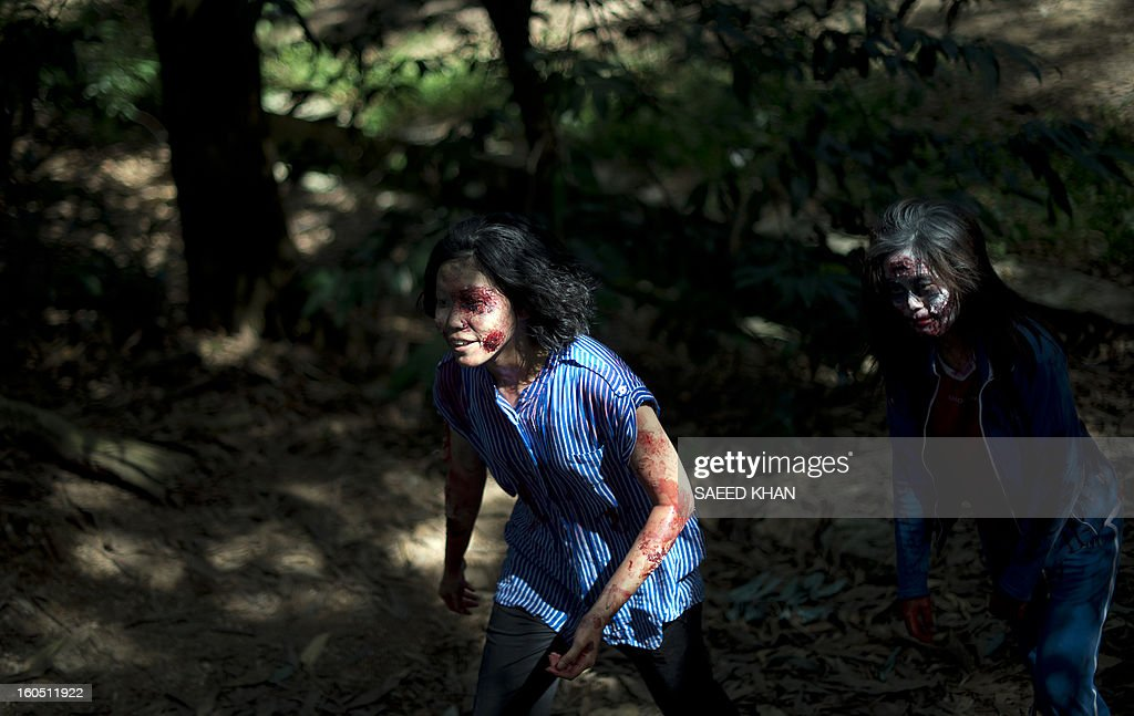 Malaysian youngsters dressed as zombies chase participants of a zombie run inside the jungle in the outskirts of Kuala Lumpur on February 2, 2013. The zombies' goal is to take away runners' tags before they reach the race's finishing point in the one-day event. Zombie runs are already popular in the US and other countries. Malaysia has long had an interest in the supernatural rooted in age-old legends. Horror films have become increasingly popular in recent years after effectively being banned in the Muslim-majority country for three decades for celebrating the other-worldly in violation of Islamic teachings. Since popular culture was allowed to relax in the past decade, horror movies have sprouted. In 2011, the genre made up more than a third of domestic movies. AFP PHOTO / Saeed KHAN