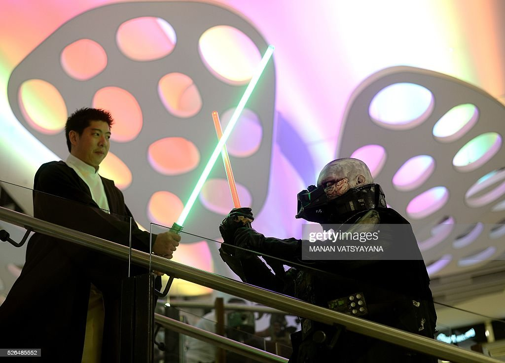 Malaysians William Wong dressed as popular 'Star Wars' character Obi Wan Kinobi (L) and Khalil Ishak dressed as Darth Vader (R) strike a pose during an event to mark the Star Wars Day celebration in Kuala Lumpur on April 30, 2016.