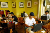 Malaysians work on their laptops at a Starbucks outlet providing wireless Internet in downtown Kuala Lumpur 16 June 2004 The availability of wireless...