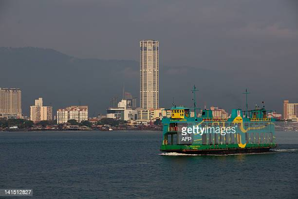 MalaysiapoliticsPenangheritageFEATURE by Dan Martin This picture taken on February 22 shows a ferry passing through Penang's landmark Komtar in...