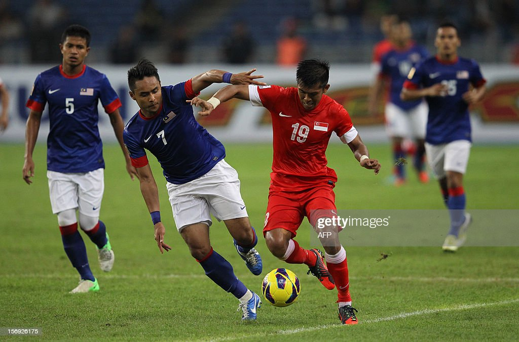 Malaysia's Aidil Zafuan Razak (2L) fights for the ball with Singapore's Khairul Amri Kamal during their AFF Suzuki Cup group B football match in Bukit Jalil Stadium outside Kuala Lumpur on November 25, 2012. AFP PHOTO / MOHD RASFAN