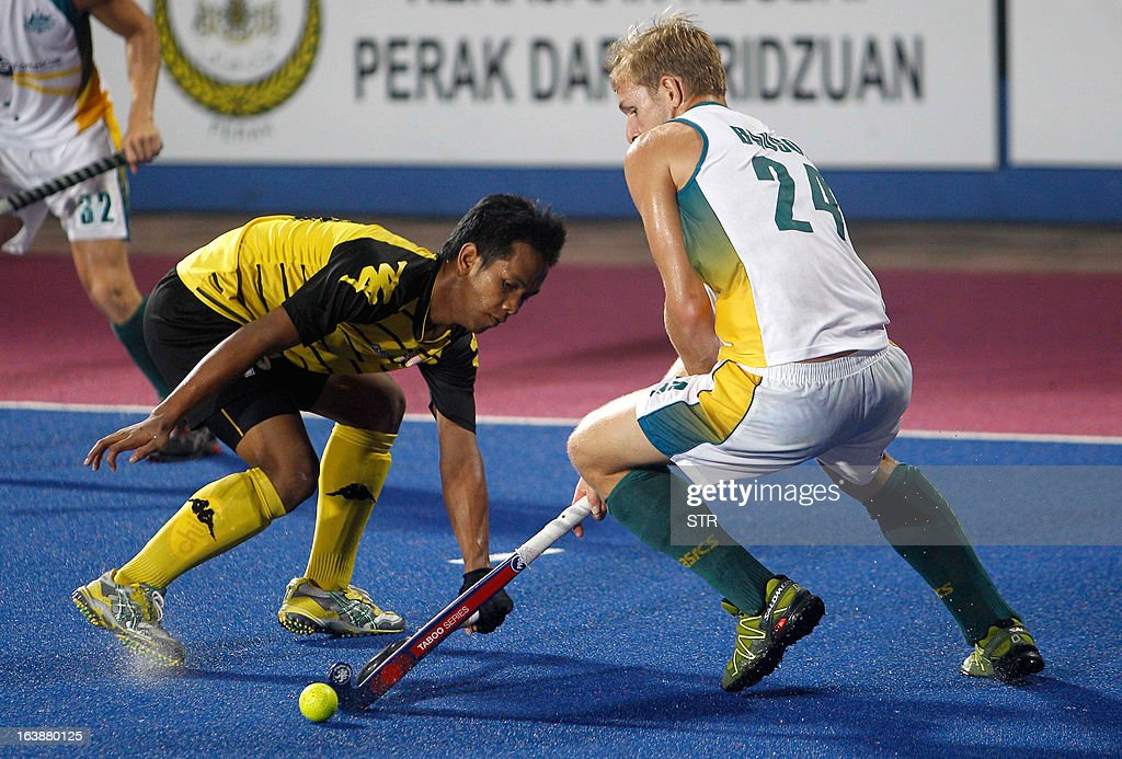 Malaysia's Faizal Saari (L) fights for the ball with Australia's Christopher Bausor during the Sultan Azlan Shah Cup men's field hockey tournament finals in Ipoh, Malaysia's northern Perak state on March 17, 2013. Australia defeated Malaysia by 3-2.