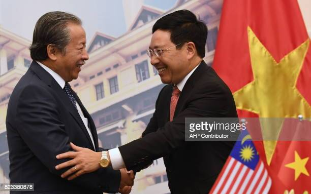 Malaysia's Foreign Minister Anifah Aman shakes hands with Vietnam's Deputy Prime Minister and Minister of Foreign Affairs Pham Binh Minh as they meet...
