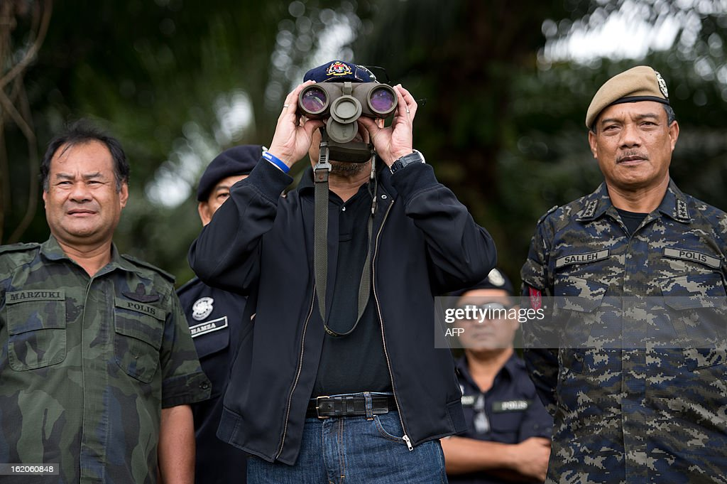Malaysia's Home Minister Hishammuddin Hussein (C) uses binoculars to view Tanduo village, where suspected Philippine militants are holding off near Lahad Datu, during his visit on February 19, 2013. Followers of a Philippine sultan who crossed to the Malaysian state of Sabah this month will not leave and are reclaiming the area as their ancestral territory, the sultan said on February 17 amid a tense standoff. AFP PHOTO / MOHD RASFAN