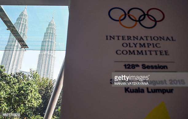 Malaysia's iconic twin towers are seen through a glass door next to a banner for the International Olympic Committee 's 128 session at the Convention...