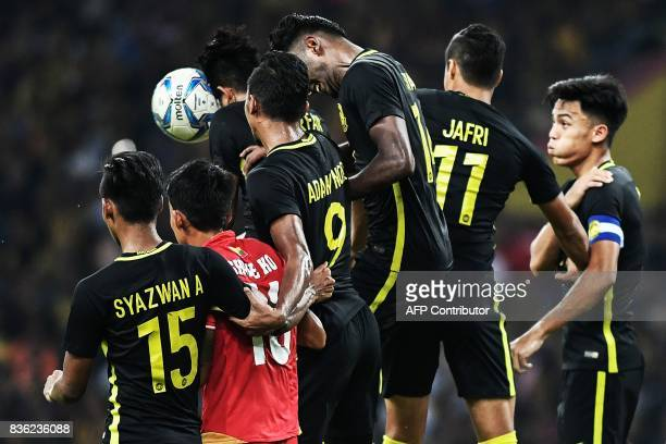 Malaysia's Irfan Zakaria heads the ball next to Myanmar's Shwe Ko during their men's football match at the 29th Southeast Asian Games at Shah Alam...