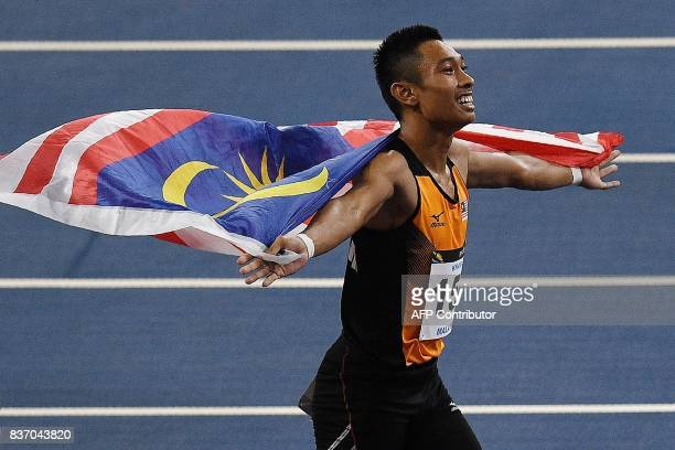 Malaysia's Khairul Hafiz celebrates after winning the men's 100m athletics final of the 29th Southeast Asian Games at the Bukit Jalil national...