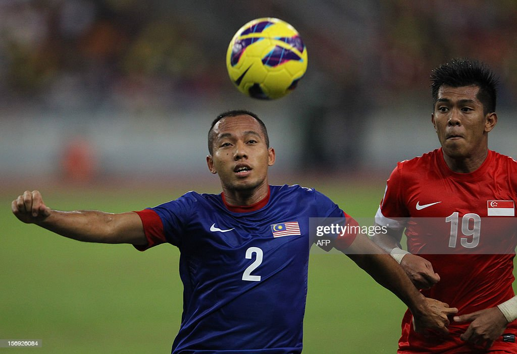 Malaysia's Mahalli Jasuli (L) heads the ball against Singapore's Khairul Amri Kamal during their AFF Suzuki Cup group B football match in Bukit Jalil Stadium outside Kuala Lumpur on November 25, 2012.