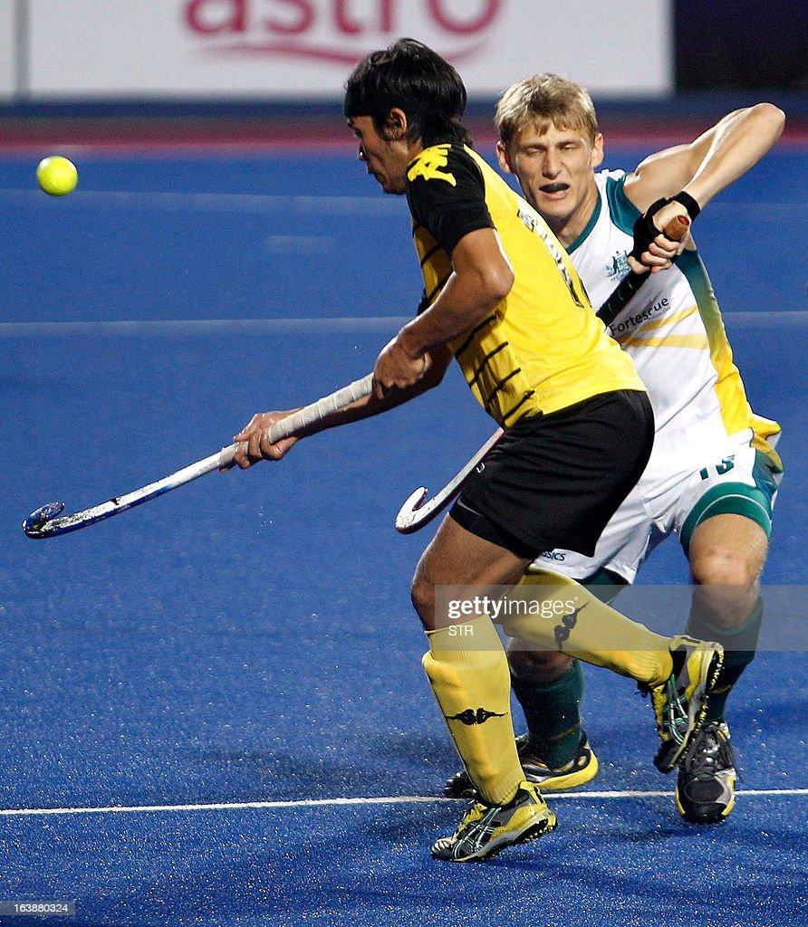 Malaysia's Mohamad Sukri Abdul Mutalib and Australia's Craig Boyne compete for the ball during the Sultan Azlan Shah Cup men's field hockey...