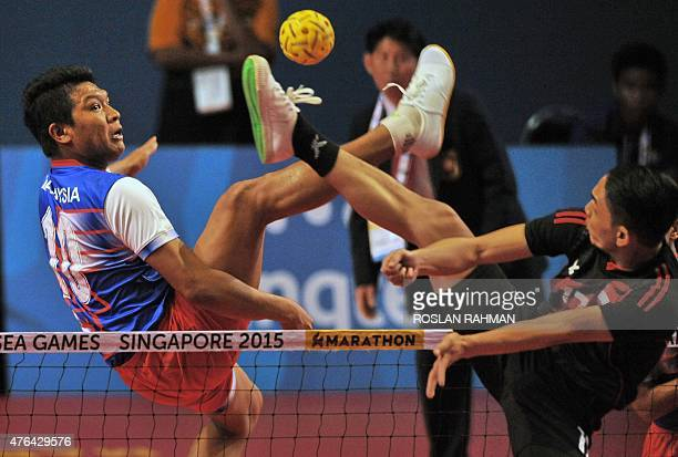 Malaysia's Mohd Zamree Mohd Dahan competes with Singapore's Muhammad Hafiz Ja'afar during the men's team sepak takraw match at the 28th Southeast...