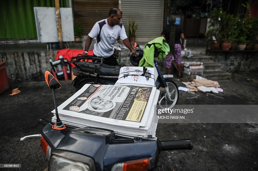 Malaysia's newspapers with reports about the Malaysia Airlines flight MH17 crashed in eastern Ukraine are seen on a motorbike for home delivery in Kuala Lumpur on July 19, 2014. Malaysia Airlines Flight MH17 carrying 298 people from Amsterdam to Kuala Lumpur crashed on July 17 in rebel-held east Ukraine, as Kiev said the jet was shot down in a 'terrorist' attack.