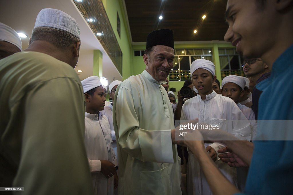 Malaysia's opposition leader Anwar Ibrahim (C) shakes hands with supporters during a visit to his constituency in Kubang Semang on April 19, 2013. Malaysia announced on April 10 a general election for May 5, setting a long-awaited date for polls tipped to be its closest ever as the long-ruling government seeks to hold off a surging opposition.