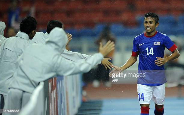 Malaysia's player Khyril Muhymeen Zambri celebrates a goal with Malaysian supporters during their AFF Suzuki Cup group B football match against Laos...