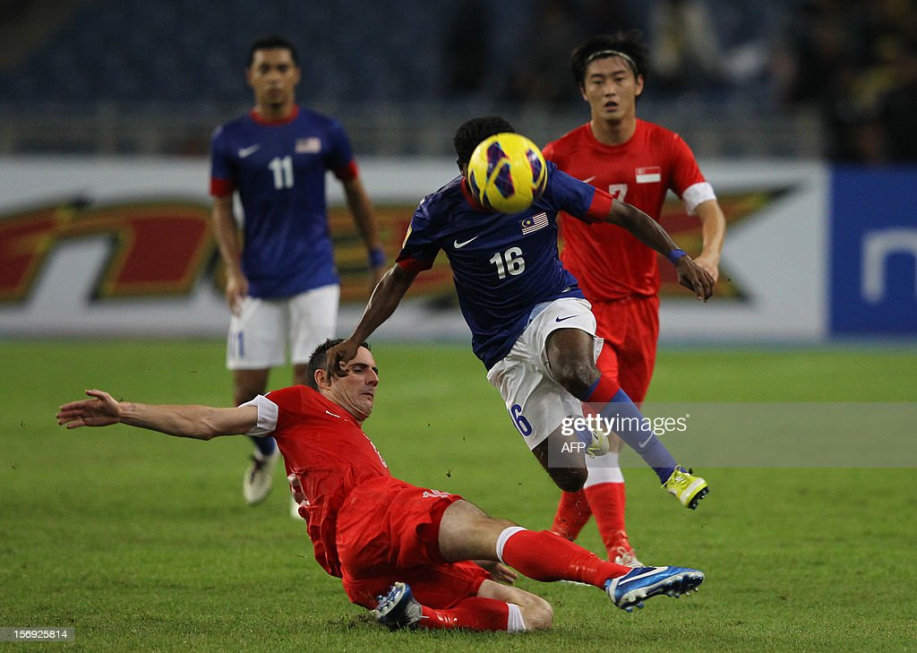 Malaysia's player Kunanlan Subramaniam (C) heads the ball against Singapore's player Daniel Bennet during their AFF Suzuki Cup group B football match in Bukit Jalil Stadium outside Kuala Lumpur on November 25, 2012.