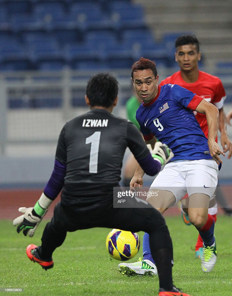 Malaysia's player Norshahrul Idlan Talaha (2nd-R) tries to shoot past Singapore's goalkeeper Mohamad Izwan Mahbud during their AFF Suzuki Cup group B football match in Bukit Jalil Stadium outside Kuala Lumpur on November 25, 2012.
