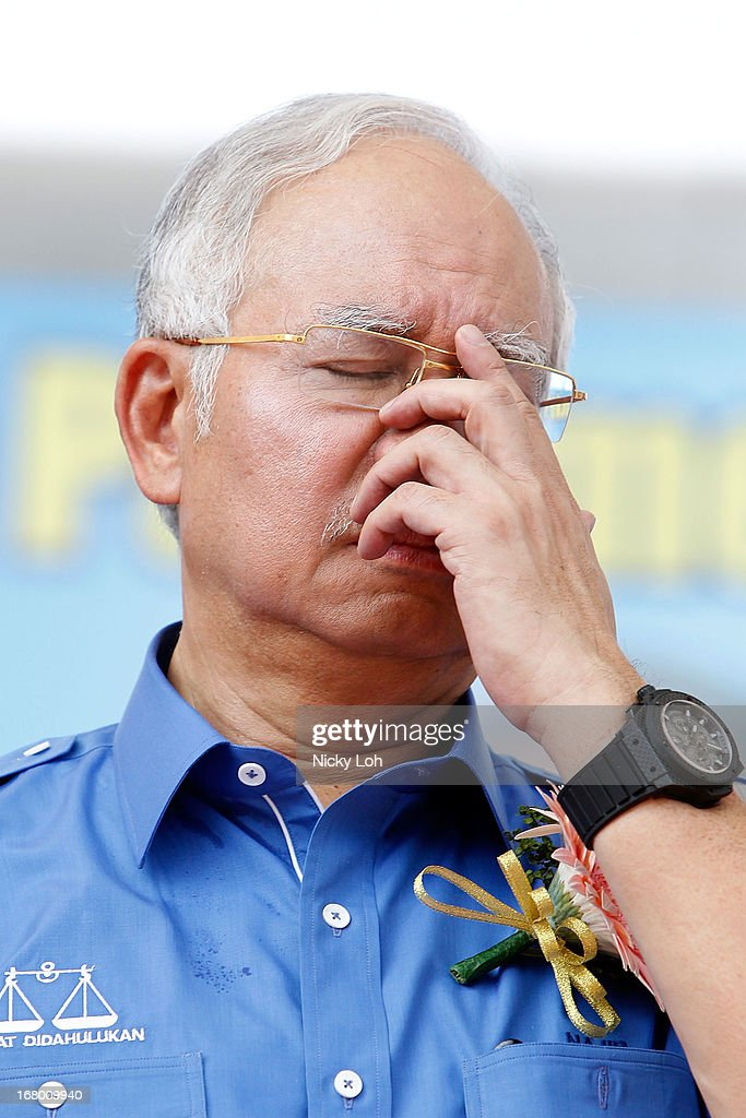 Malaysia's Prime Minister and Barisan Nasional (BN) chairman Najib Razak adjusts his spectacles as he greets supporters during an election rally to address young parliamentary constituency voters at his hometown on May 4, 2013 in Pekan, Malaysia. The election, set for May 5, will see incumbent PM Najib Razak face Anwar Ibrahim, whose opposition coalition includes moderates, Islamists and Malaysians of Chinese descent