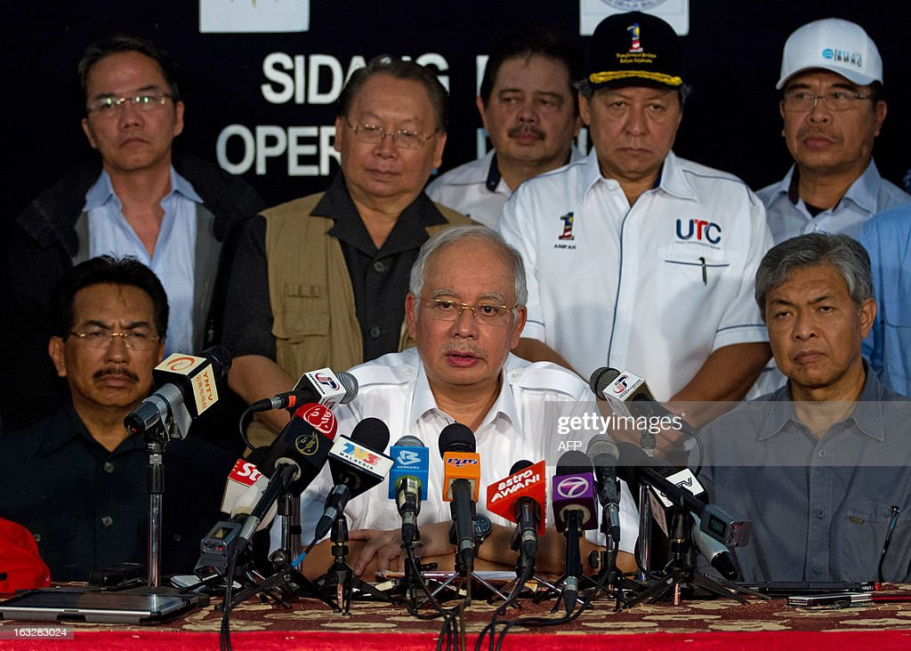 Malaysia's Prime Minister Najib Razak (C-front), accompanied by Malaysian Defence Minister Zahid Hamidi (front-R), speaks during a press conference in Felda Sahabat in Lahad Datu on March 7, 2013 concerning the situation in Malaysia's Sabah statte where Philippine militants following a self-styled sultan recently launched a deadly incursion. Malaysia's defence minister on March 7 rejected a ceasefire offer by the self-styled Philippine sultan unless his fighters who launched a deadly incursion 'surrender unconditionally'.