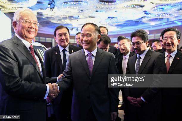 Malaysia's Prime Minister Najib Razak and Chairman of the Zheijiang Geely Holding Group Li Shufu shake hands after the signing ceremony between...