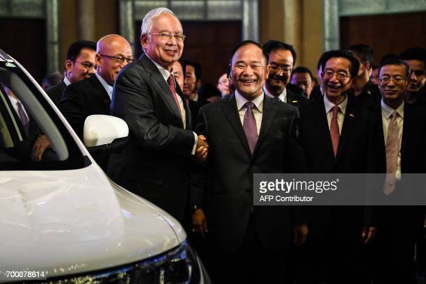 Malaysia's Prime Minister Najib Razak and Chairman of the Zheijiang Geely Holding Group Li Shufu smile after the signing ceremony between DRBHICOM...