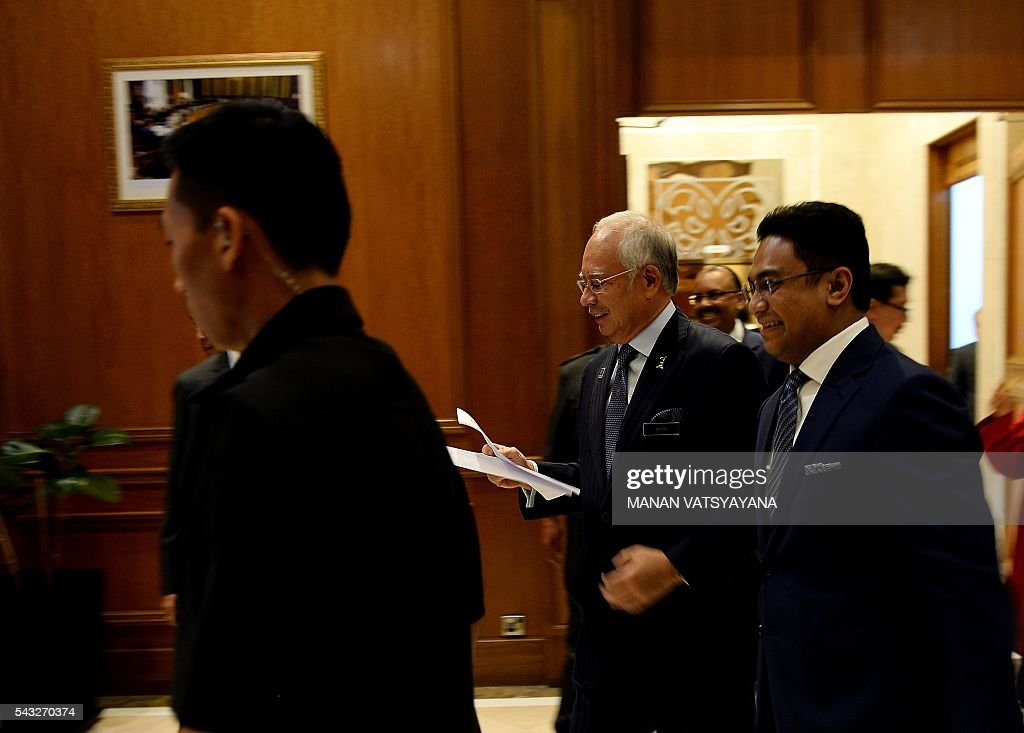 Malaysia's Prime Minister Najib Razak (C) arrives to address the media following a cabinet reshuffle at his office in Putrajaya on June 27, 2016. Scandal-hit Malaysian Prime Minister Najib Razak Monday announced a cabinet reshuffle, including promoting a trusted ally to manage the economy, in what analysts said could be preparation for a snap election. / AFP / MANAN