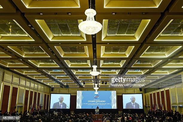 Malaysia's Prime Minister Najib Razak is pictured on large video screens as he addresses the opening ceremony for the 48th ASEAN Foreign Ministers...