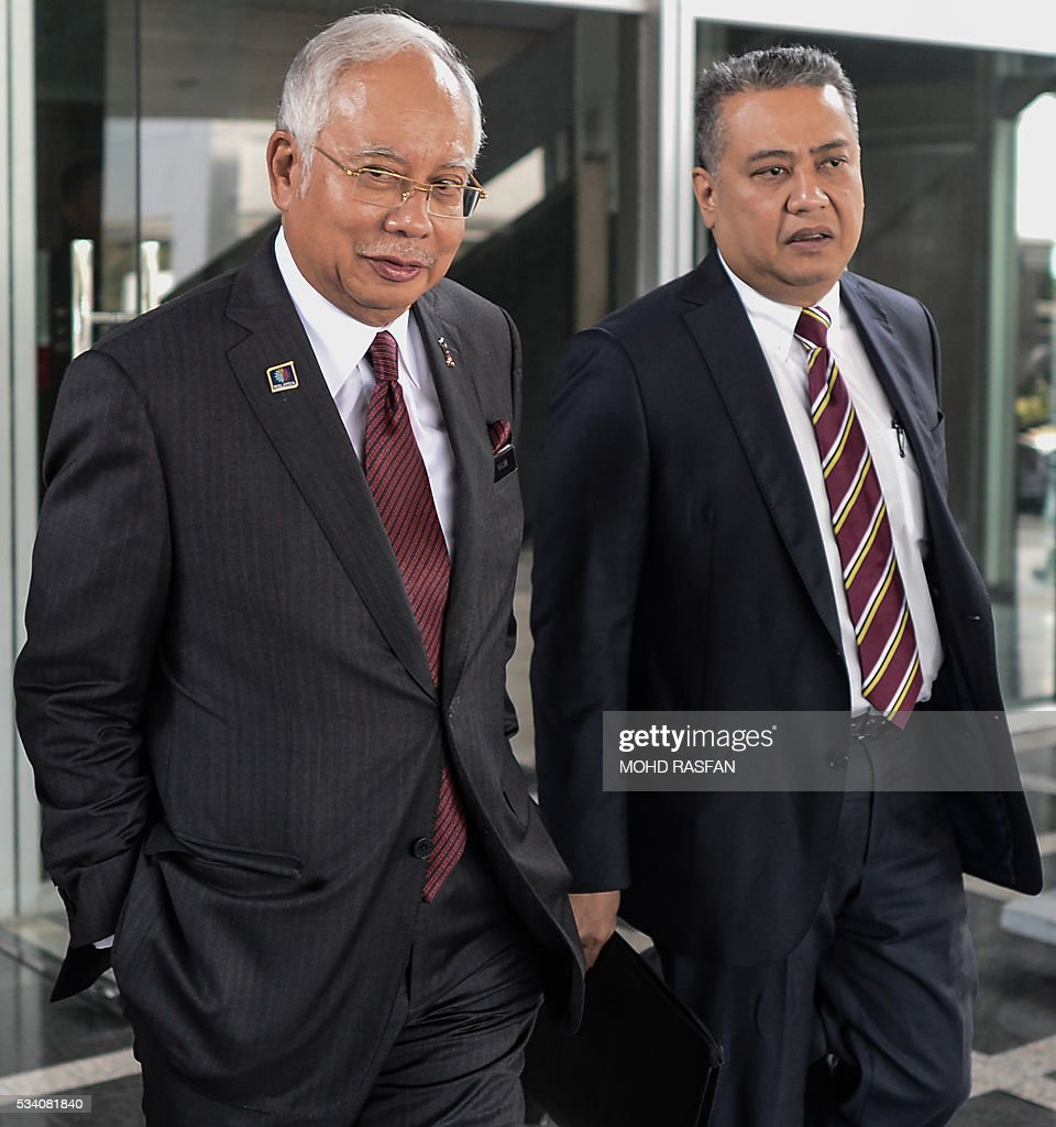 Malaysia's Prime Minister Najib Razak (L) leaves his office at the parliament in Kuala Lumpur on May 25, 2016. Swiss financial regulators approved on May 24 the dissolution of Lugano-based BSI Bank over its links to a corruption scandal engulfing Malaysia's Prime Minister Najib Razak. / AFP / MOHD
