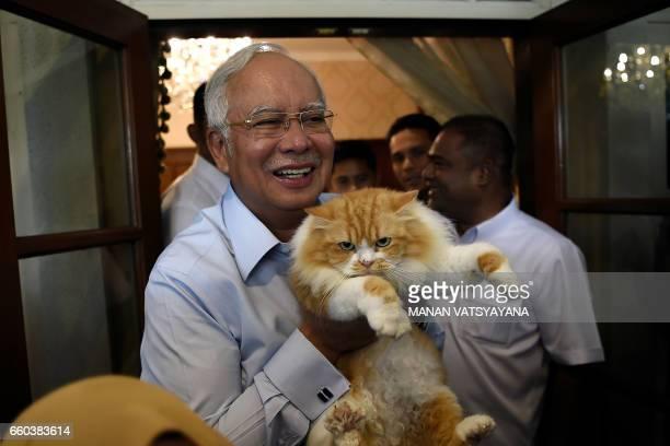 Malaysia's Prime Minister Najib Razak poses with his cat Kiki at his residence in Kuala Lumpur on March 30 2017 / AFP PHOTO / Manan VATSYAYANA