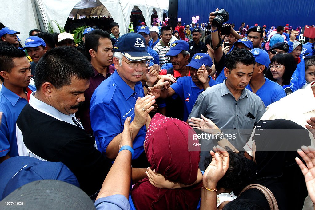 Malaysia's Prime Minister Najib Razak (2nd L), president of the ruling party National Front, greets supporters as he arrives for a campaign event ahead of the 13th country's general elections in Pekan Nenas, a town located in Pontian district of Johor on April 29, 2013. Opposition leader Anwar Ibrahim held a slight edge in support over Malaysian Premier Najib Razak, according to a survey released on April 26 ahead of a hotly anticipated election showdown on May 5. MALAYSIA