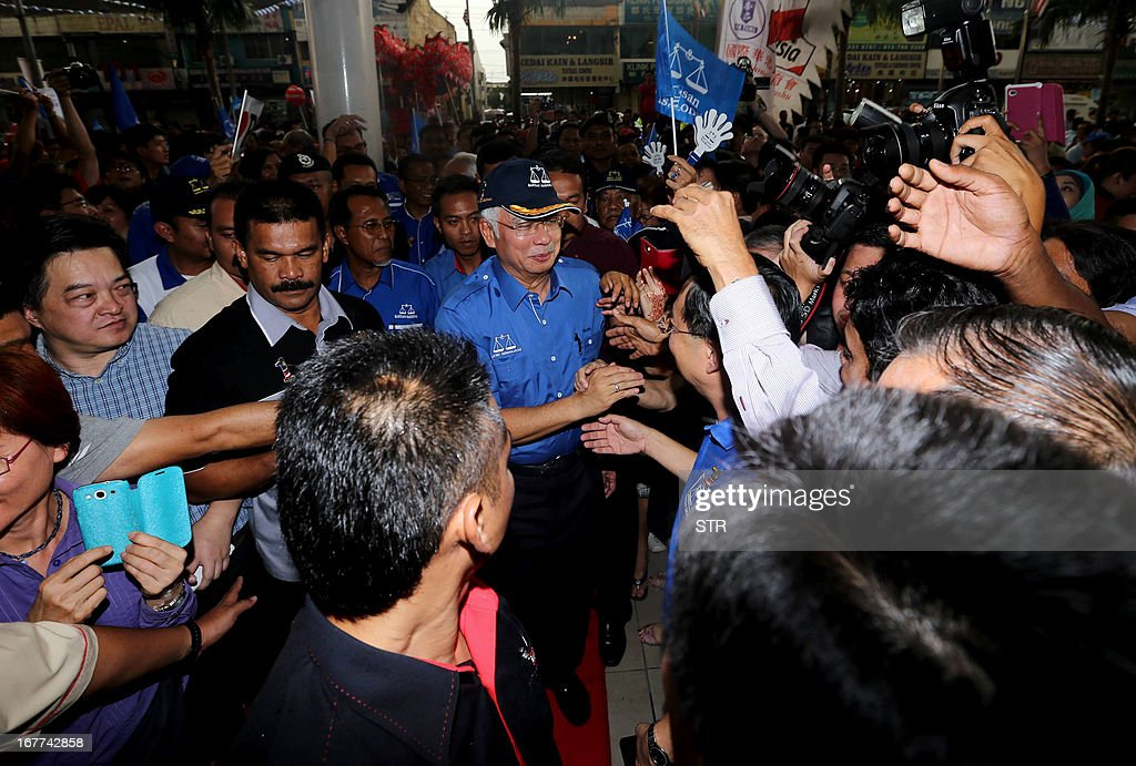 Malaysia's Prime Minister Najib Razak (C), president of the ruling party National Front, greets supporters as he arrives to a campaign event ahead of general elections in Pekan Nenas, a town located in Pontian district of Johor on April 29, 2013. Opposition leader Anwar Ibrahim held a slight edge in support over Malaysian Premier Najib Razak, according to a survey released on April 26 ahead of a hotly anticipated election showdown on May 5. MALAYSIA