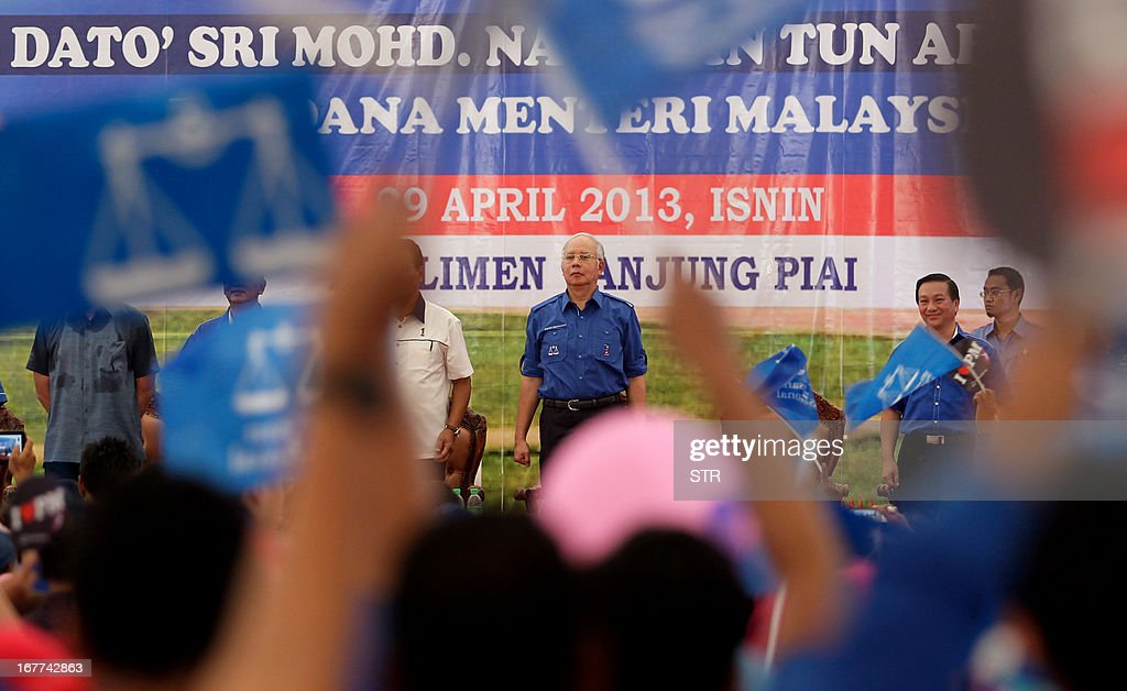 Malaysia's Prime Minister Najib Razak (C), president of the ruling party National Front, stands for the national anthem during a campaign event ahead of general elections in Pekan Nenas, a town located in Pontian district of Johor on April 29, 2013. Opposition leader Anwar Ibrahim held a slight edge in support over Malaysian Premier Najib Razak, according to a survey released on April 26 ahead of a hotly anticipated election showdown on May 5. MALAYSIA