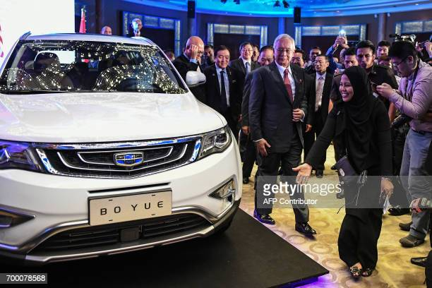 Malaysia's Prime Minister Najib Razak walks next to first public viewing of the Geely Boyue SUV car after the signing ceremony between DRBHICOM...