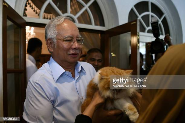 Malaysia's Prime Minister Najib Razak watches as his cat Kiki is carried at his residence in Kuala Lumpur on March 30 2017 / AFP PHOTO / Manan...